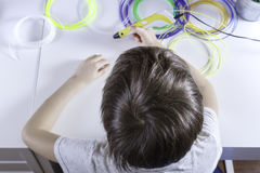 Barn som skapar med pennan för printing 3D Pojke som gör det nya objektet Idérikt teknologi, fritid, utbildningsbegrepp Arkivbilder