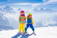Barn som skidar i bergen Arkivbild