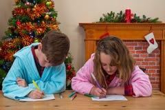 Barn som skrivar brev till jultomten Arkivbilder