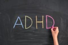 Barn som skriver f?rkortningen ADHD p? en svart tavla arkivbilder