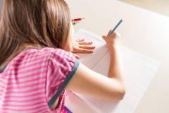 Barn som skriver henne homwork på ett skrivbord med en blå blyertspennafärgpenna Fotografering för Bildbyråer
