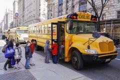 Barn som skriver in skolbussen Royaltyfri Bild