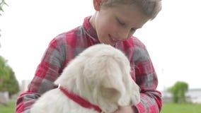 Barn som slår och kramar hans vän för älsklings- djur Pys som spelar med hans hund i parkera