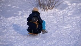 Barn som sledding ner en snöig kulle långsam rörelse stock video