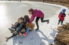 Barn som sledding på ett djupfryst damm Arkivfoto