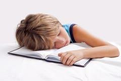 barn som sover med boken Royaltyfria Bilder