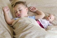 Barn som sover med dockan Royaltyfri Foto