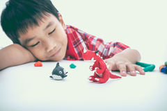 Barn som sover med hans arbeten från lera, på vit Förstärk th Arkivfoto