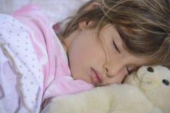 Barn som sover med nallebjörnen Arkivfoton