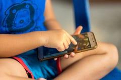 Barn som spelar den smarta telefonen Arkivfoton