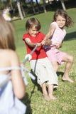 Barn som spelar dragkampen Arkivfoton