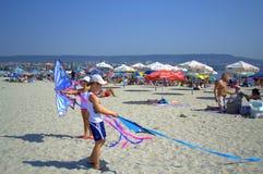 Barn som spelar drakar på stranden Arkivbild