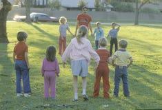 Barn som spelar en lek på ett offentligt, parkerar, den trädgårds- dungen, CA Royaltyfri Fotografi