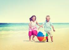 Barn som spelar för strandsommar för lycka gladlynt begrepp Arkivbild