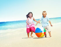 Barn som spelar för strandsommar för lycka gladlynt begrepp Arkivfoton