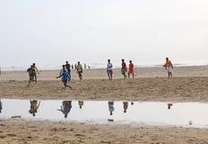 Barn som spelar fotboll i stranden, Indien Arkivbild
