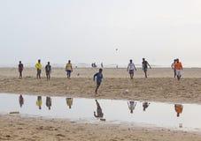 Barn som spelar fotboll i stranden, Indien Arkivfoto