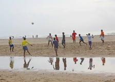 Barn som spelar fotboll i stranden, Indien Arkivbilder