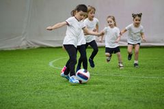 Barn som spelar fotboll inomhus Ungar som kör på fältet Lite är pojken klar att sparka bollen royaltyfri fotografi