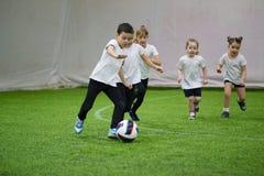 Barn som spelar fotboll inomhus Ungar som kör på fältet Lite pojke som leder bollen arkivbilder