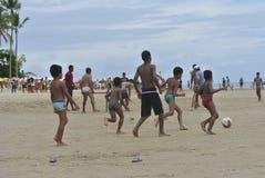 Barn som spelar fotboll på stranden royaltyfri fotografi