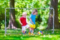 Barn som spelar fotboll utomhus arkivfoton