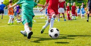 Barn som spelar fotbollfotbollleken på sportfält Pojkelekfotbollsmatch på grönt gräs Lag för ungdomfotbollturnering royaltyfria bilder