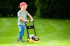 Barn som spelar gräsklippningsmaskingräs Royaltyfria Bilder
