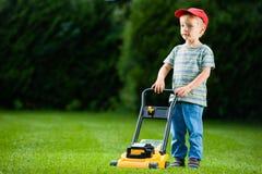 Barn som spelar gräsklippningsmaskingräs Royaltyfria Foton