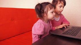 Barn som spelar i bärbara datorn Två små flickor skrivs ut på en bärbar dator Två systrar som sitter på den orange soffan som ser arkivfilmer