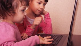 Barn som spelar i bärbara datorn Två små flickor skrivs ut på en bärbar dator Två systrar som sitter på den orange soffan som ser lager videofilmer