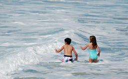 Barn som spelar i bränningen i Laguna Beach, Kalifornien Arkivbilder