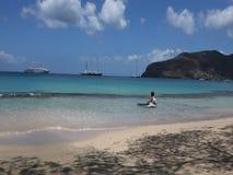 Barn som spelar i det karibiska havet med passagerarefartyg i bakgrunden lager videofilmer