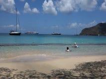 Barn som spelar i det karibiska havet med passagerarefartyg i bakgrunden stock video