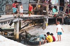 Barn som spelar i det smutsiga vattnet i Koh Rong royaltyfri fotografi