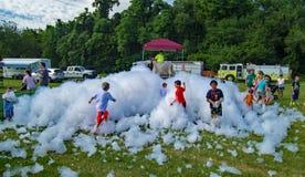 Barn som spelar i Firemen's skum fotografering för bildbyråer