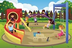 Barn som spelar i lekplatsen Arkivbild