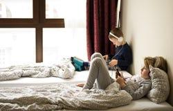 Barn som spelar i säng med deras minnestavlor och telefoner royaltyfria foton