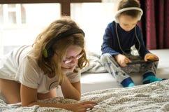 Barn som spelar i säng med deras minnestavlor och telefoner Arkivbilder