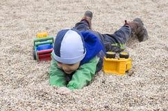 Barn som spelar i stenkiselstenar på lekplatsen Arkivfoton