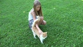 Barn som spelar katten i trädgård som skrattar flickaståenden med kattungen, djura husdjur för unge stock video