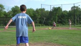 Barn som spelar Kickball i en parkera stock video
