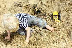 Barn som spelar lastbilar i sandlåda Fotografering för Bildbyråer
