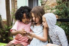 Barn som spelar lekar på en smartphone arkivfoto