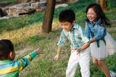 Barn som spelar lekar utomhus Arkivfoton