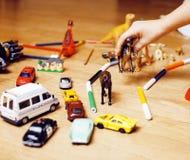Barn som spelar leksaker på golv hemma, liten hand i röra, fri utbildning arkivfoto