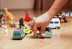Barn som spelar leksaker på golv hemma, lite Arkivbilder