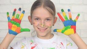 Barn som spelar målade händer som in camera ser och att le skolaflickaframsidan, ungar arkivfoton