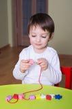 Barn som spelar med bildande pryda med pärlor för leksaker Royaltyfri Foto