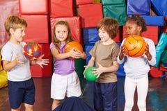 Barn som spelar med bollar i idrottshall Arkivfoton